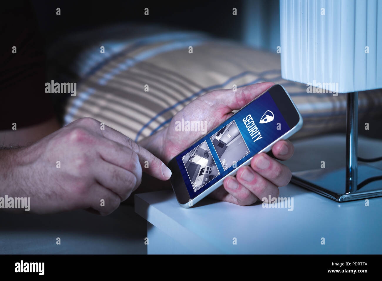 Man using home security system and application in smartphone. Watching protection and surveillance camera live footage inside a house or apartment. - Stock Image