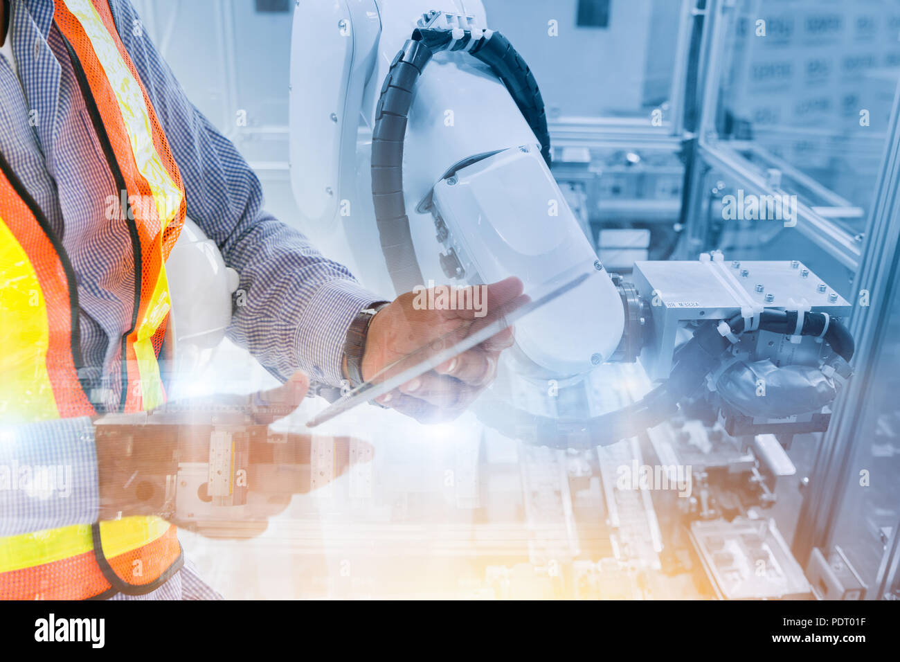worker using tablet control robot arm in production line for robotic engineering concept - Stock Image
