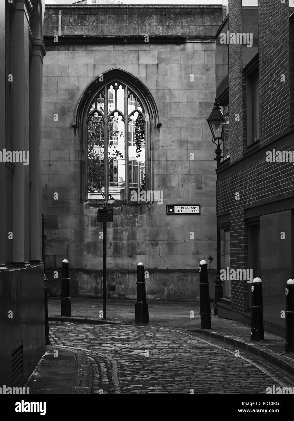 Black and white image of atmospheric street with cobblestone in London. Stone wall with gothic style window - Stock Image