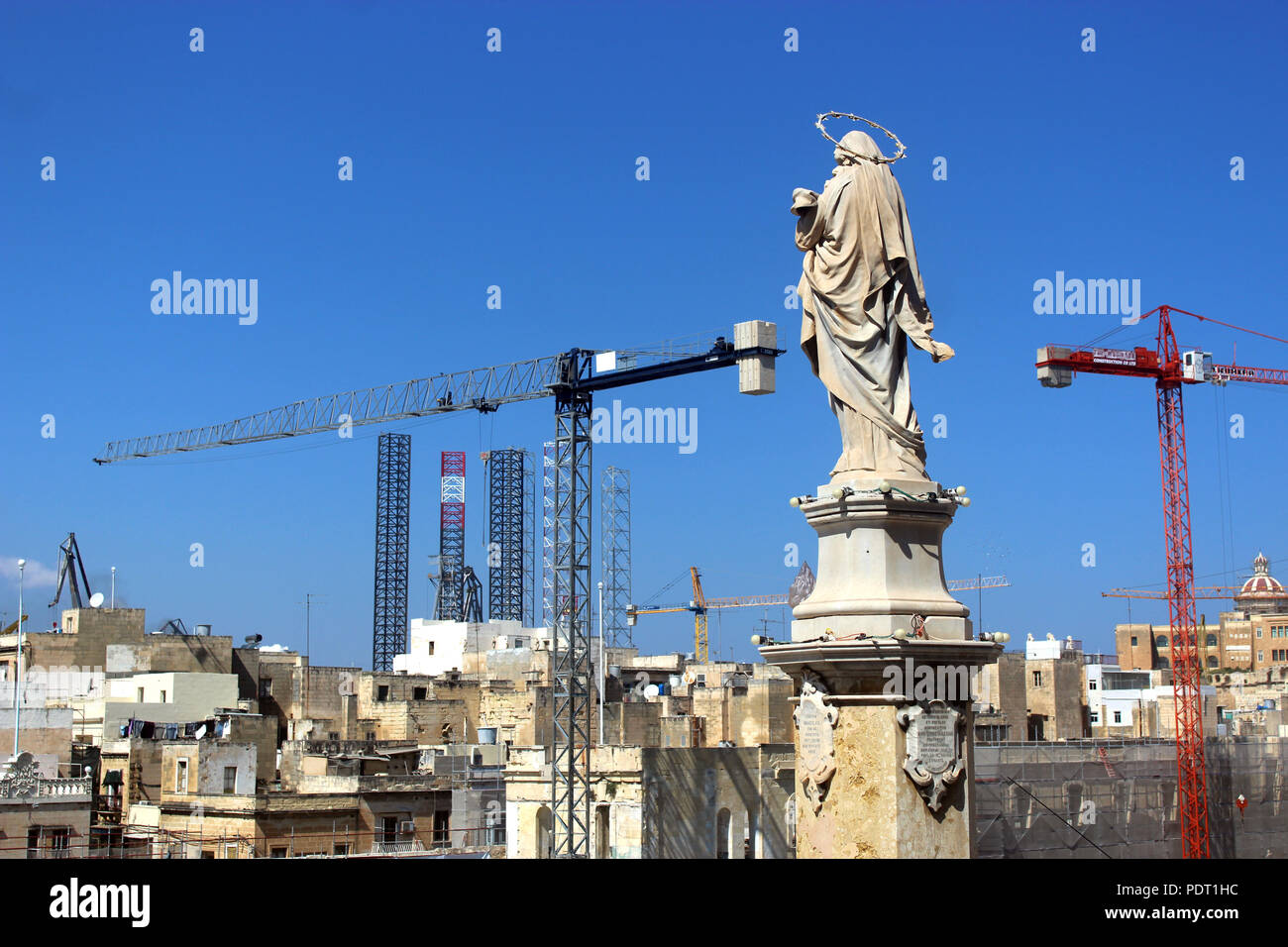 faith and progress: construction cranes beside a statue of the Virgin Mary - Stock Image