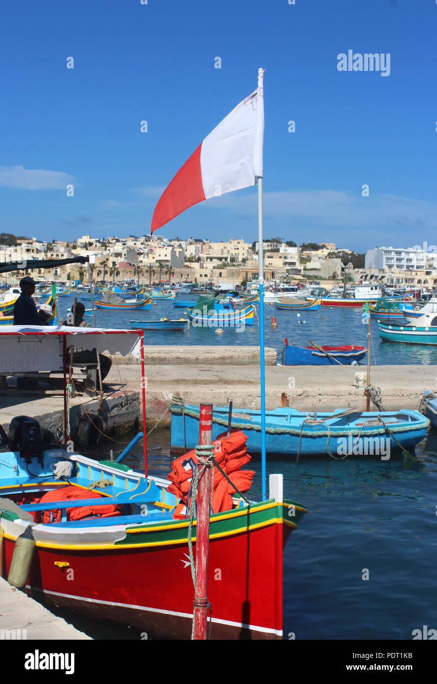 colorful traditional fishing boat with Maltese flag in Marsaxlokk, Malta, a fishers village - Stock Image