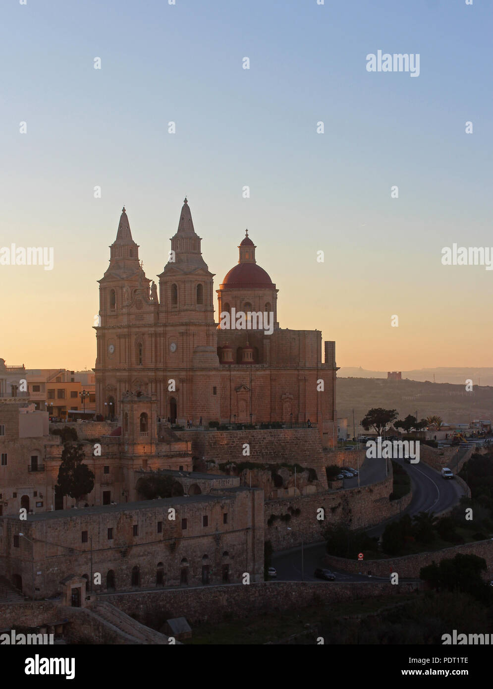 Mellieha, Malta, with its big church, at sunset, vertical - Stock Image