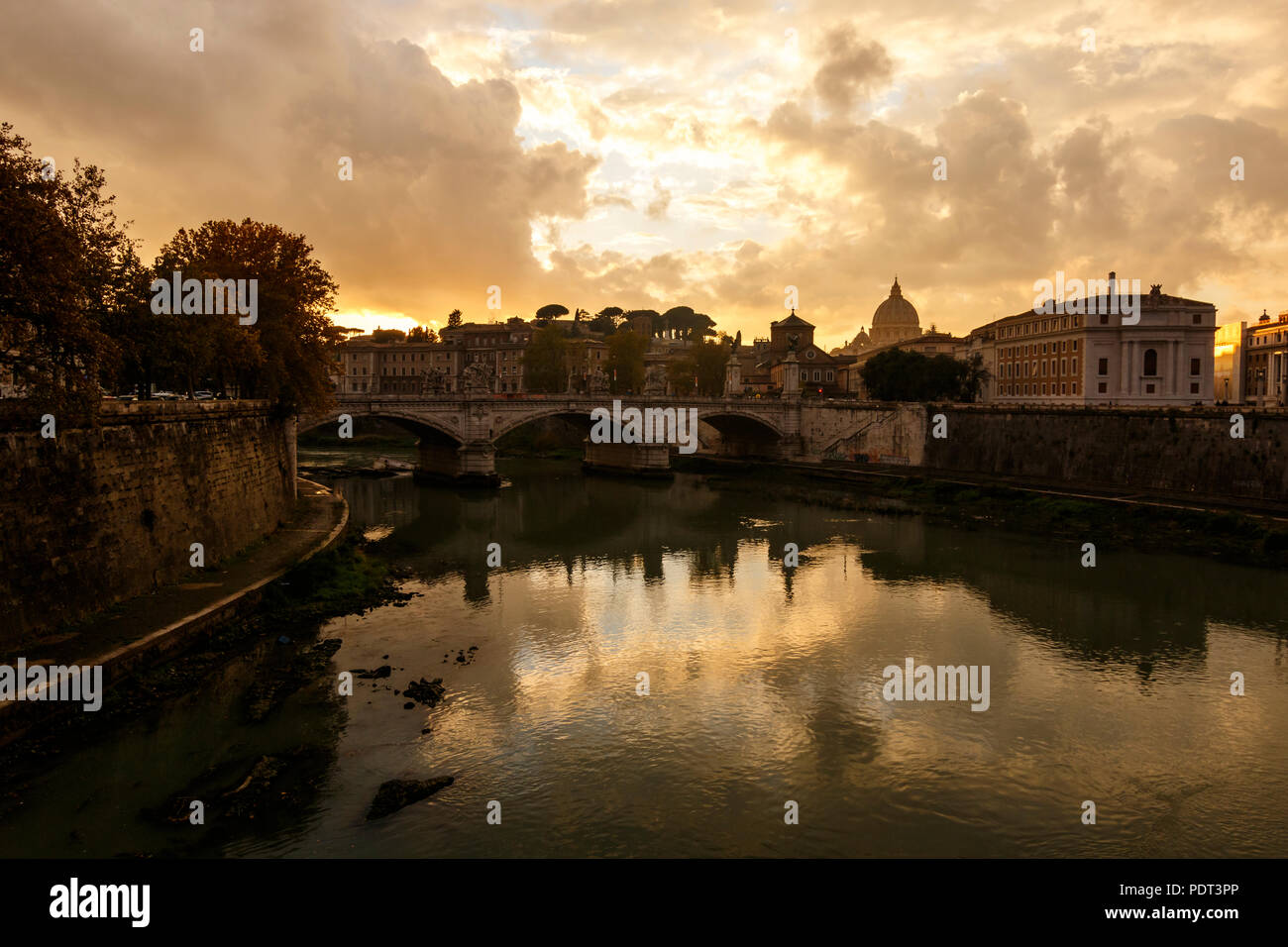 A view over the Tiber river with the Vittorio Emanuele II bridge and St. Peter's Basilica at the end. Rome, Italy. - Stock Image