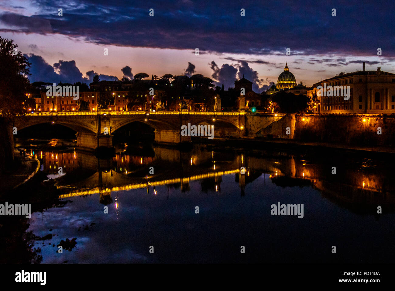 A view over Tiber river with Vittorio Emanuele II bridge and St. Peter's Basilica at Rome, Italy. - Stock Image