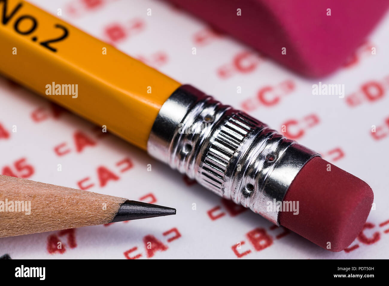A 1:1 macro of the eraser end and the sharpened end of two #2 pencils laying by an eraser on a scantron answer sheet waiting to be used to take a stan - Stock Image
