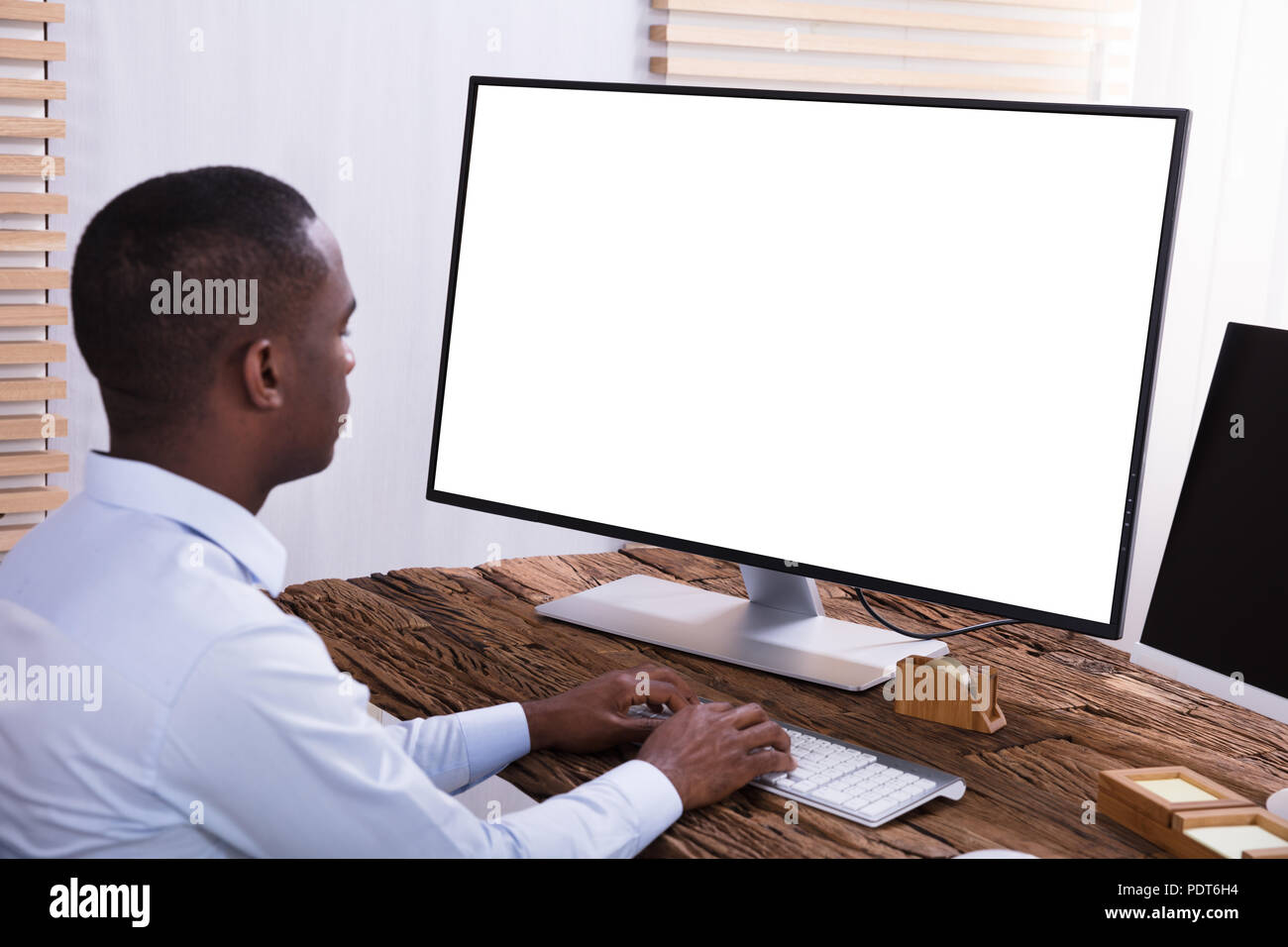 Close-up Of A Businessman Using Computer With Blank White Screen On The Wooden Desk - Stock Image