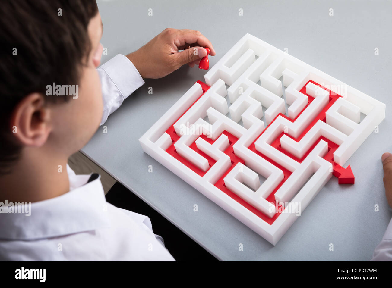 Elevated view of businessman solving maze on desk - Stock Image