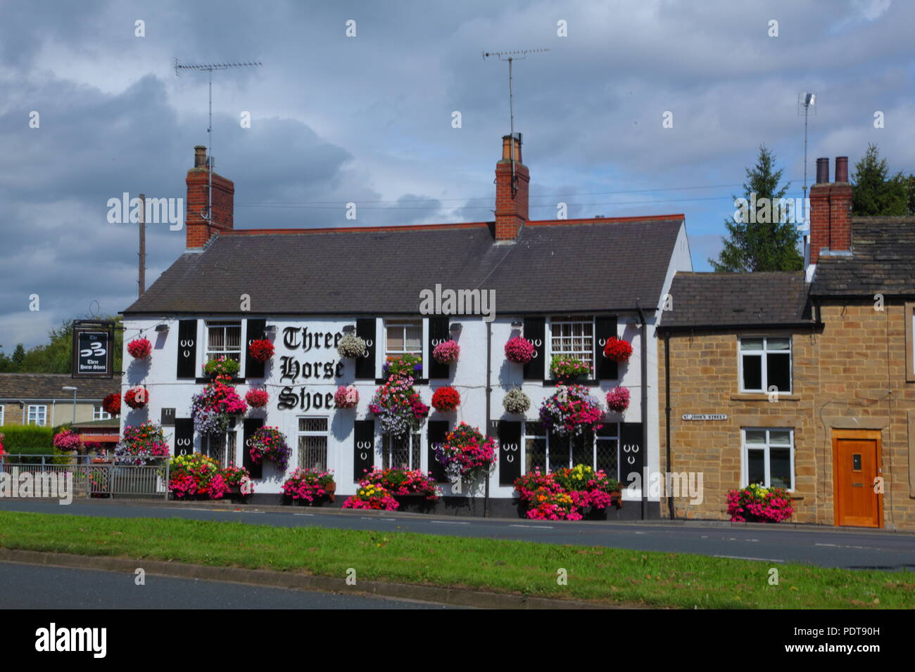 The Three Horse Shoes Pubic House & Restaurant covered in decorated hanging baskets. - Stock Image