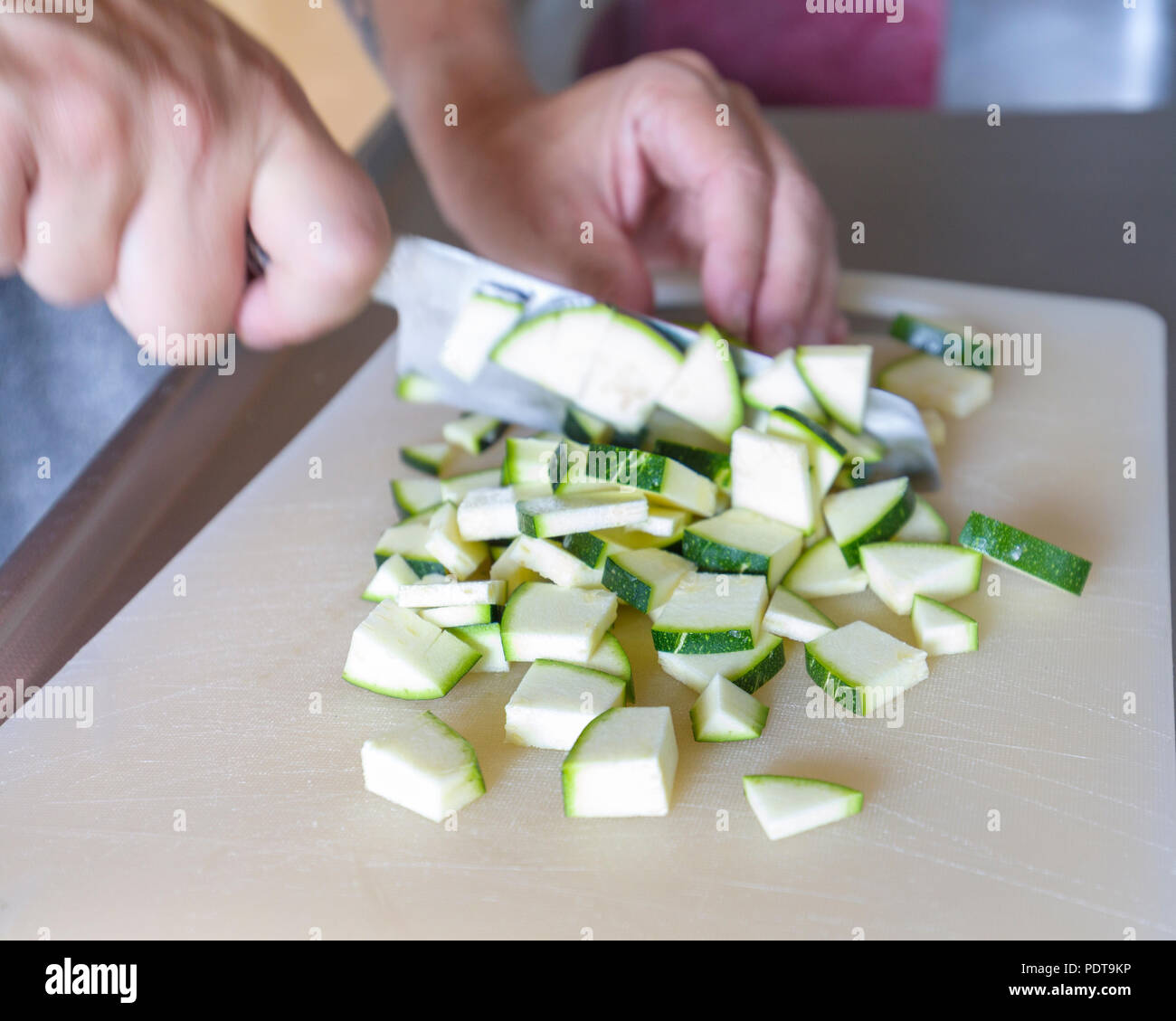 Close up view of person's hands chopping Zucchini aka Courgette with kitchen knife in preparation for dinner meal - Stock Image