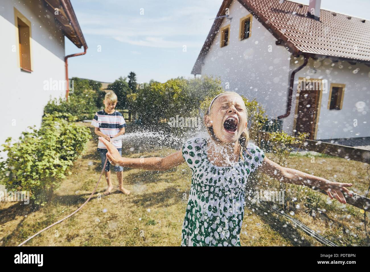 Children having fun with splashing water. Siblings on the back yard of the house during summer day. - Stock Image