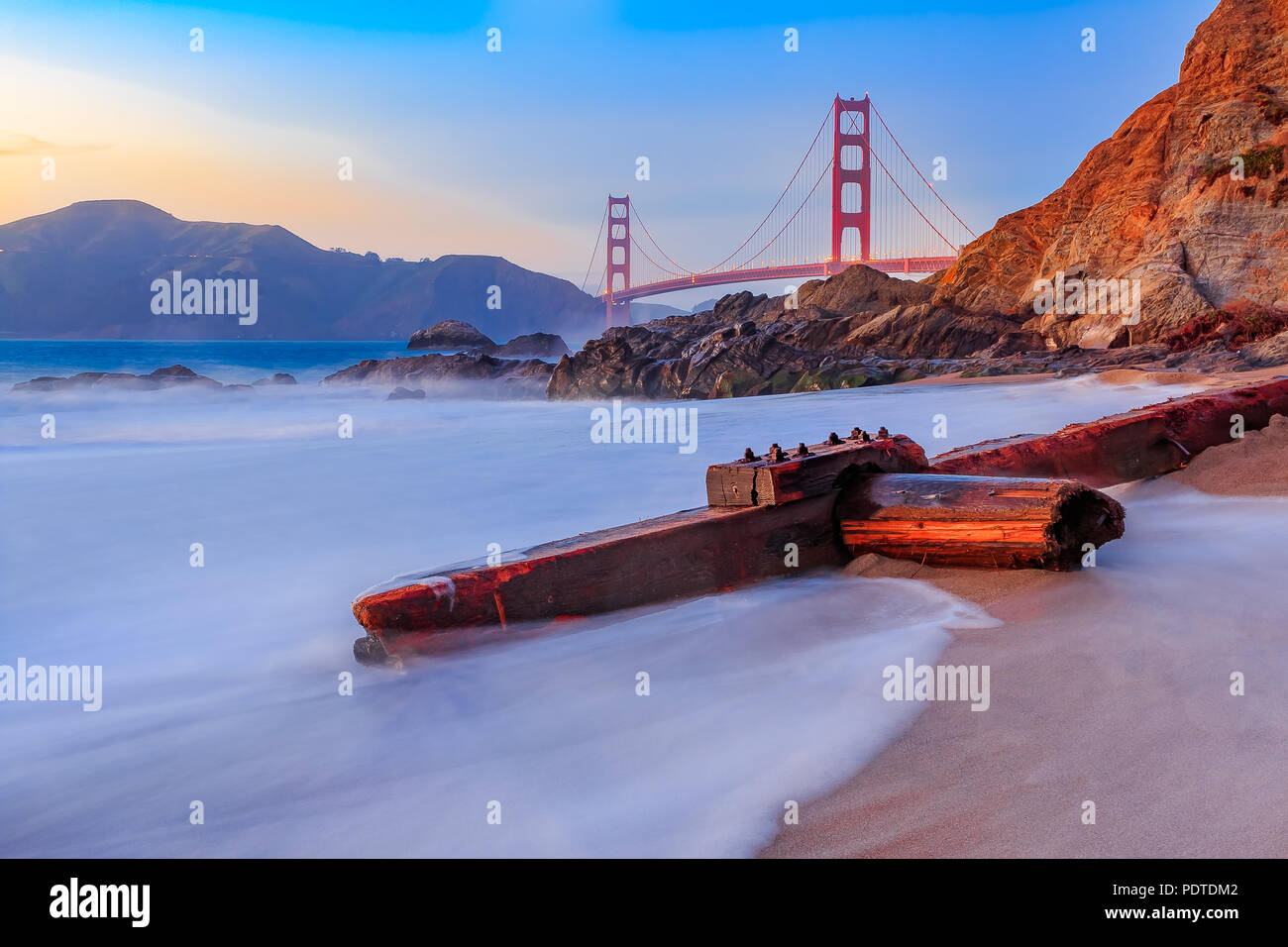 Famous Golden Gate Bridge view from Baker Beach at sunset in San Francisco, California - Stock Image