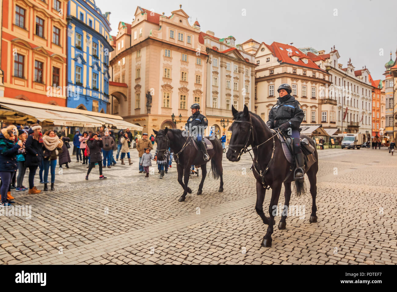 Prague, Czech Republic - January 15, 2015: Czech mounted police officers on horses in the Old Town Square and people walking in the street - Stock Image