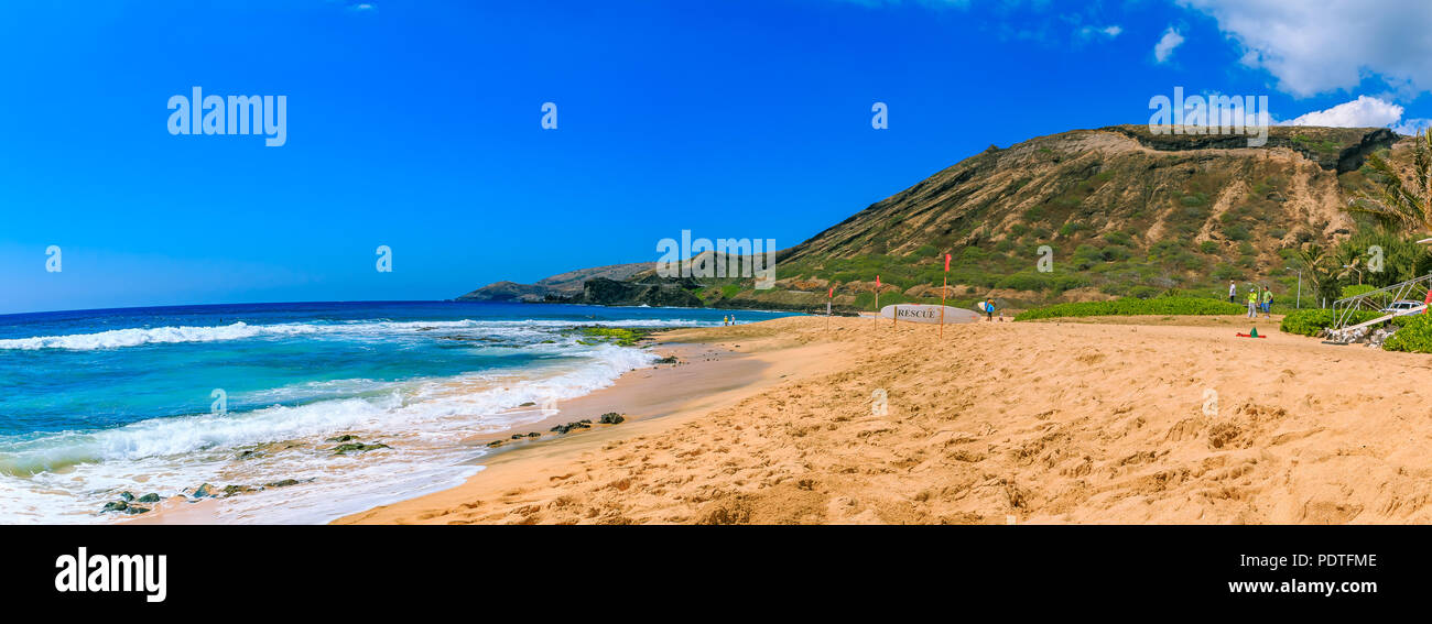 Tropical sandy beach with a volcano crater in the background in Oahu, Hawaii - Stock Image