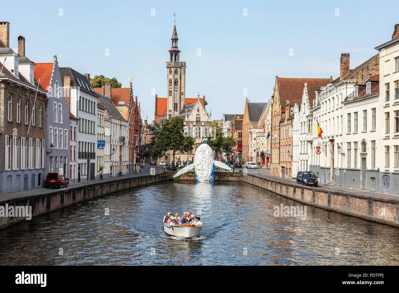 Tourists in a canal tour boat viewing the Bruges Plastic Whale sculpture made from discarded plastic containers and waste washed up from the sea, - Stock Image