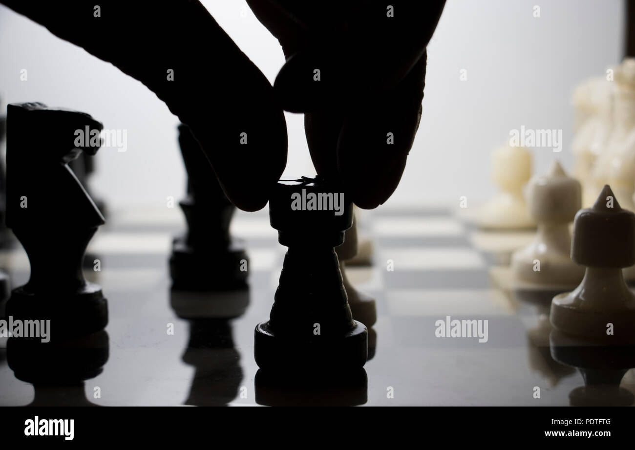 Chess game being played. Finger moving chess piece in silhouette. - Stock Image