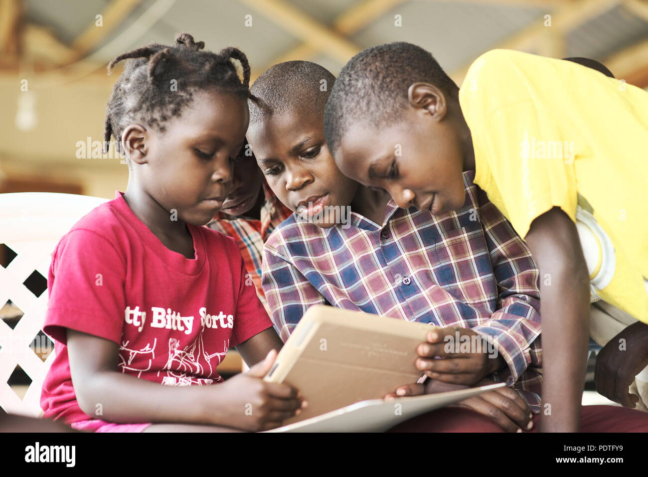 Group of young wealthy ugandan children wearing smart modern clothes gather in a group taking turns to use an IPAD - Stock Image