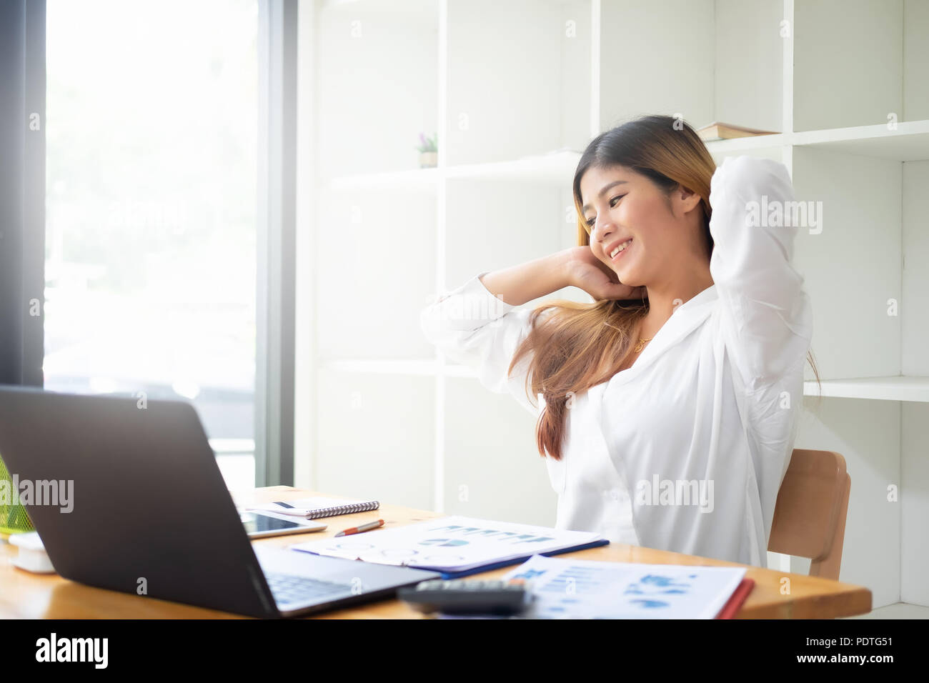 Businesswoman relaxing at comfortable in office hands behind head, happy woman resting in office satisfied after work. - Stock Image