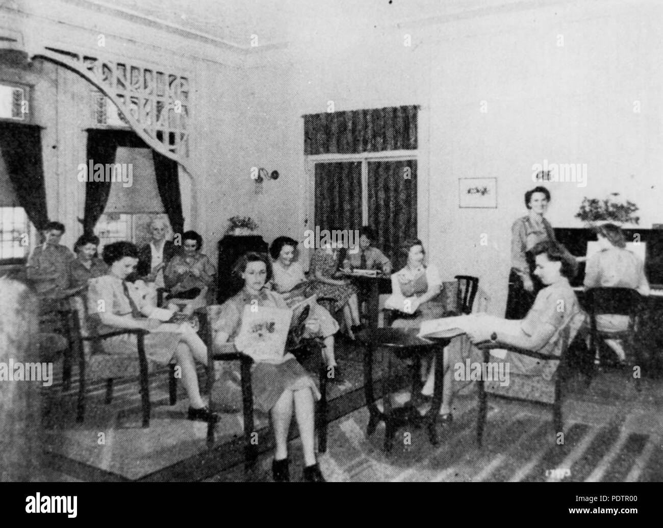 200 StateLibQld 1 103067 Group of servicewomen in the lounge room at 'Wairuna' in Highgate Hill, Brisbane in the 1940s - Stock Image