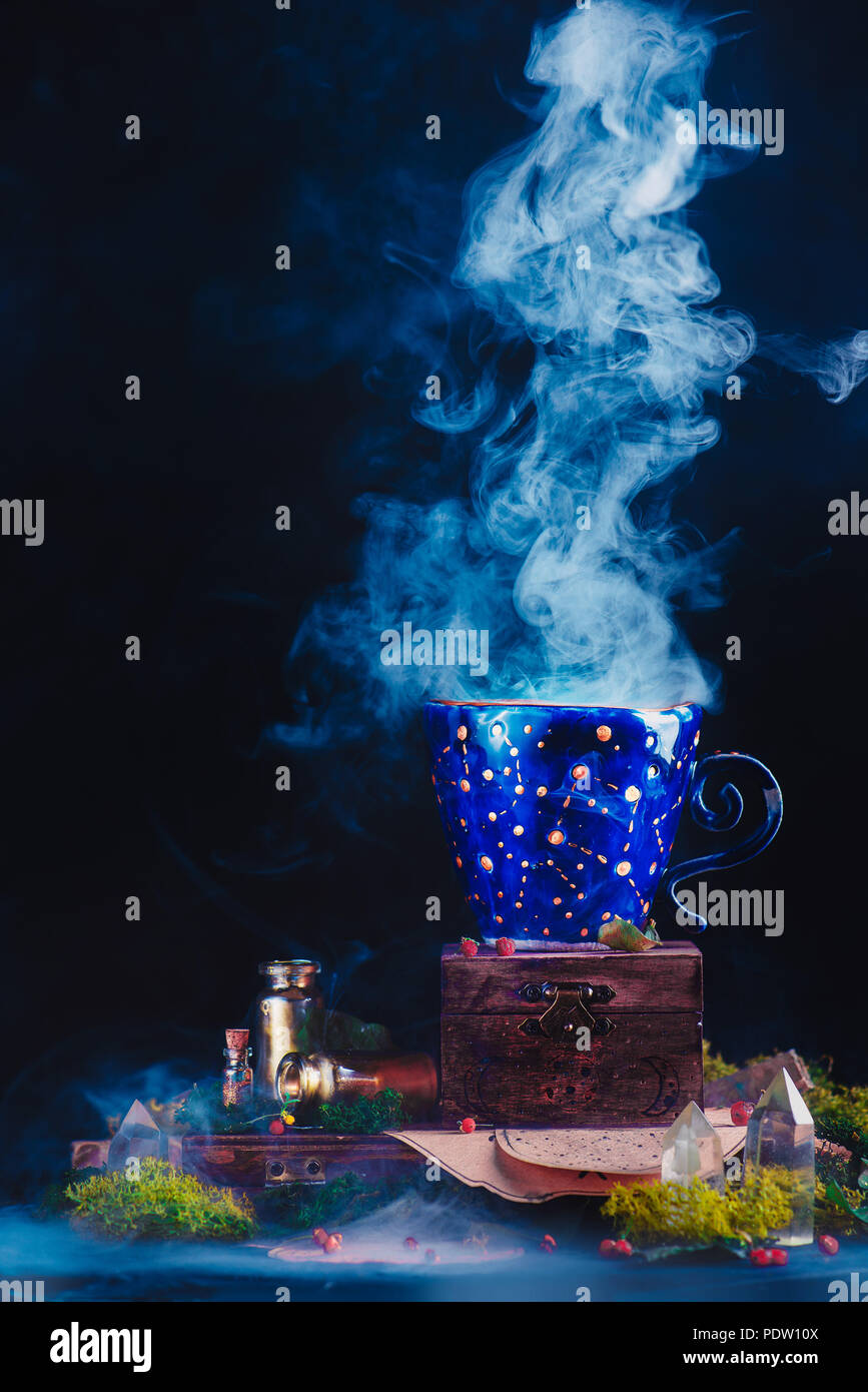 Ceramic cup with constellations and stars in a magical still life. Astronomer or astrologer workplace with smoke, crystals, moss and potion bottles. M - Stock Image
