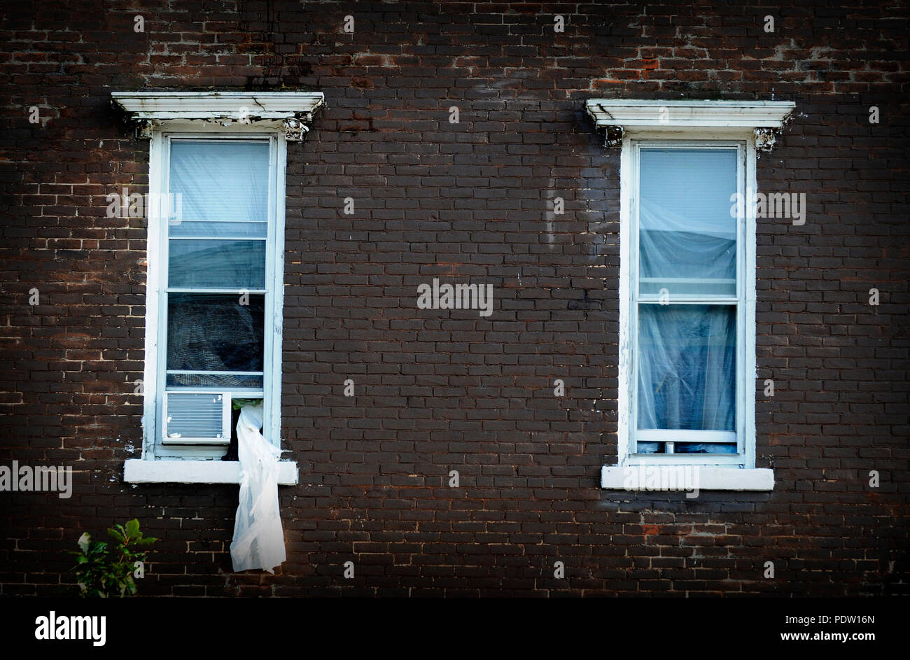 A curtain hangs out of one of the windows of a hotel in an old building. - Stock Image