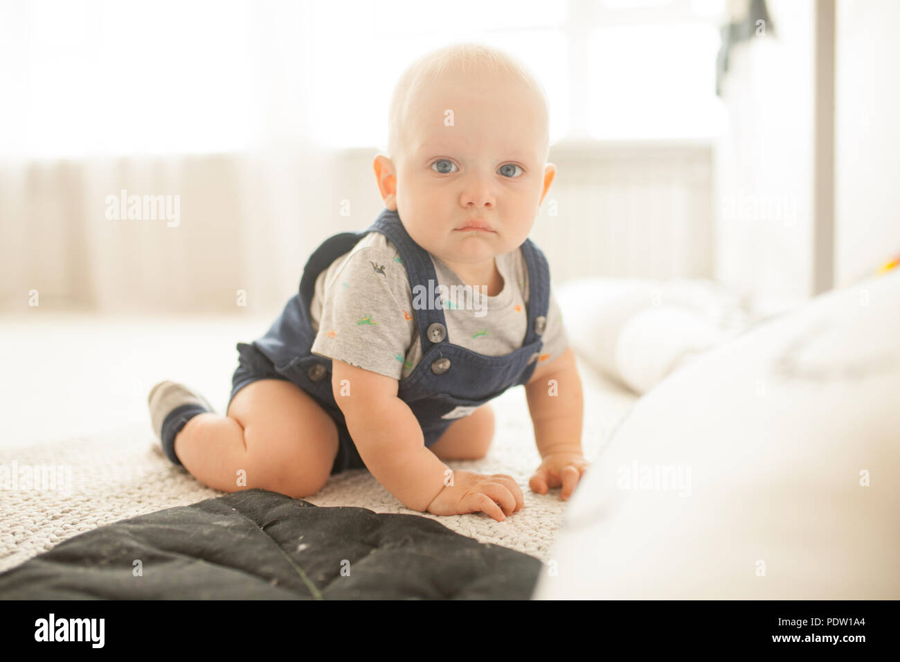 Sad toddler in rompers and t-shirt crawls on carpet in room against window. - Stock Image
