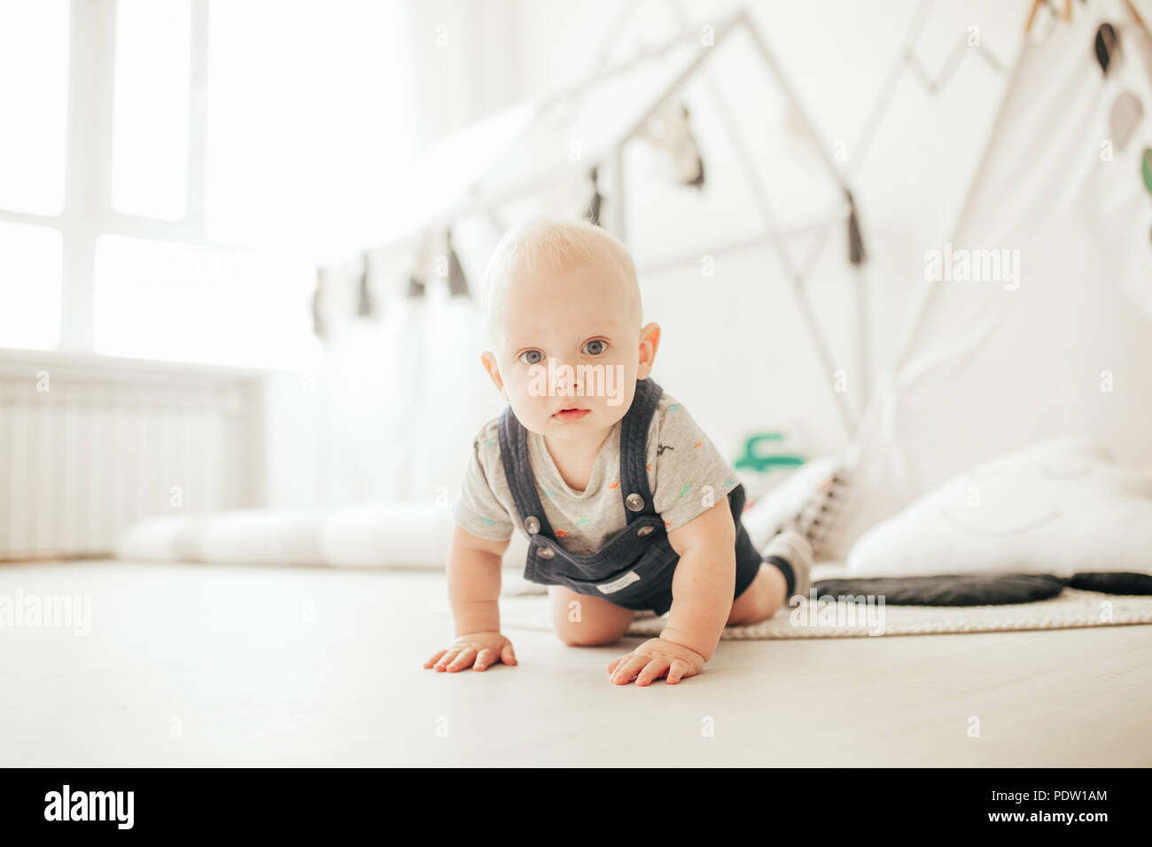 Toddler in rompers and t-shirt crawls on floor in room against window. - Stock Image