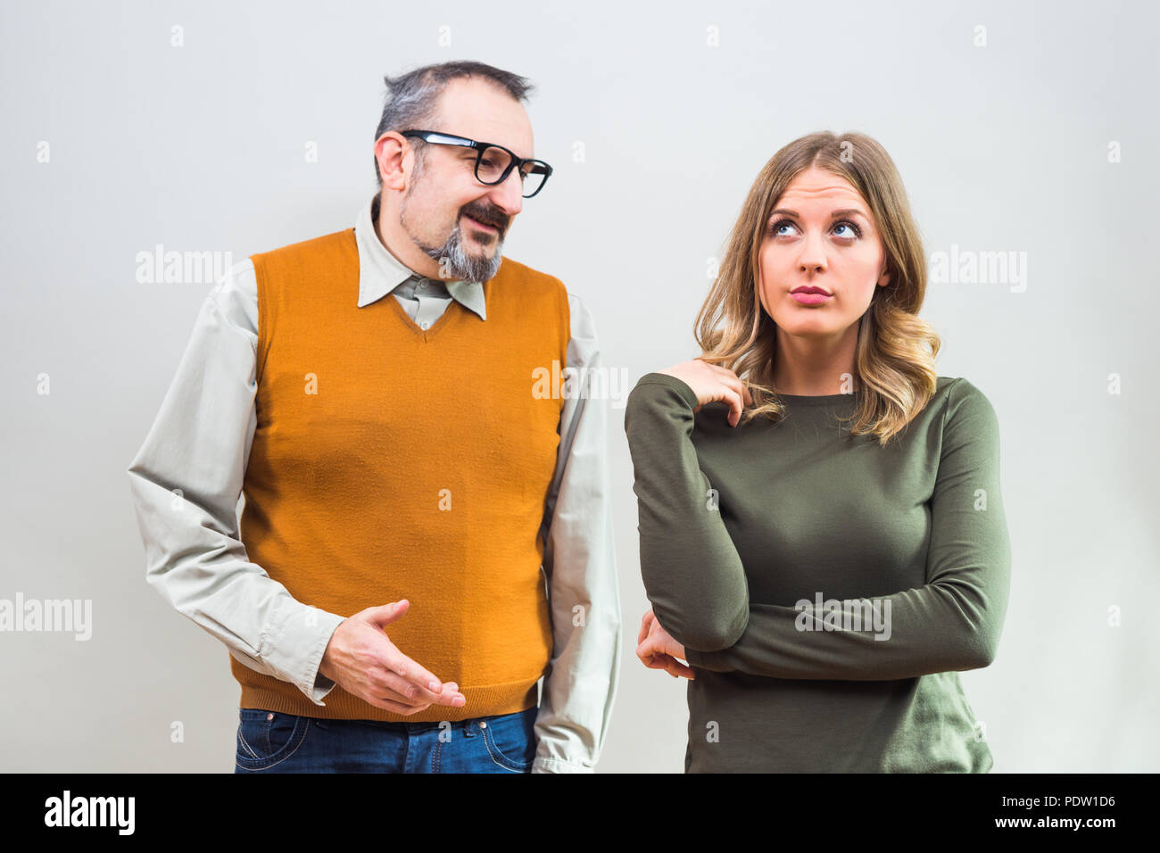 Nerdy man is trying to get beautiful woman's attention but she is not interested and angry ignore him. - Stock Image