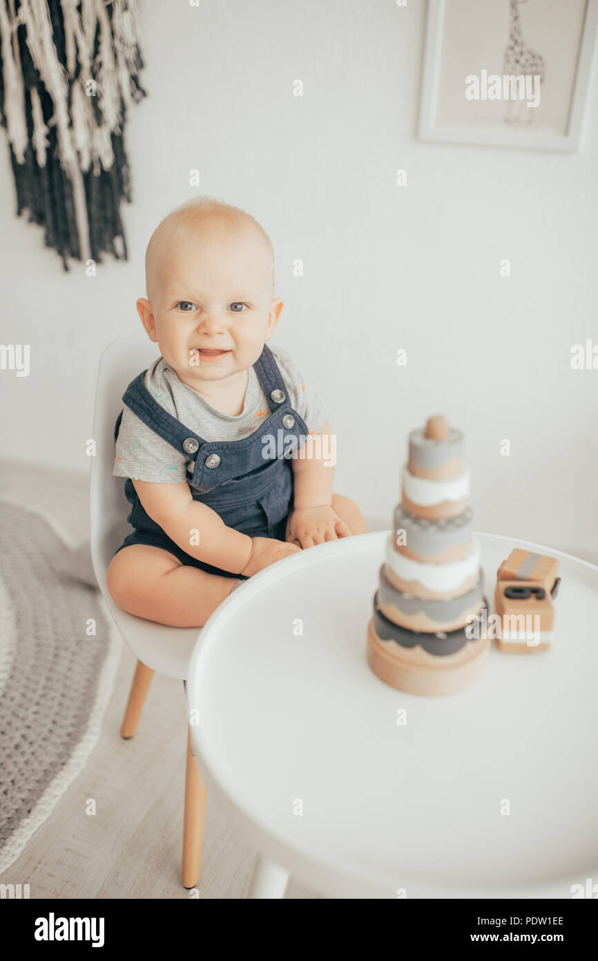 Toddler in rompers and t-shirt sits on chair next to table with toys. - Stock Image
