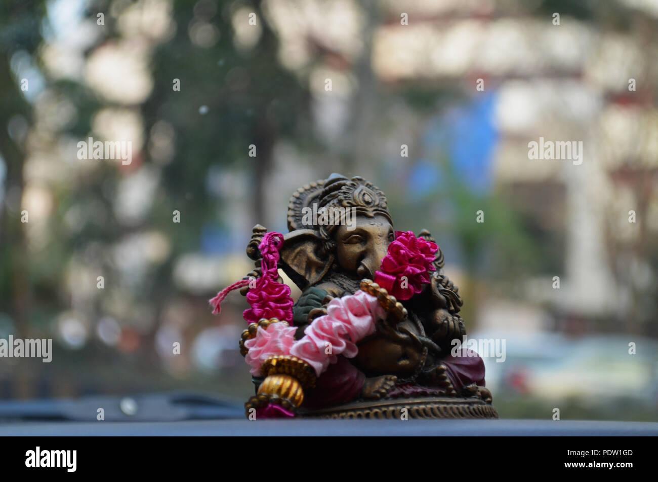 Hindu Elephant God Ganesha Bronze Idol On A Car Dashboard Stock