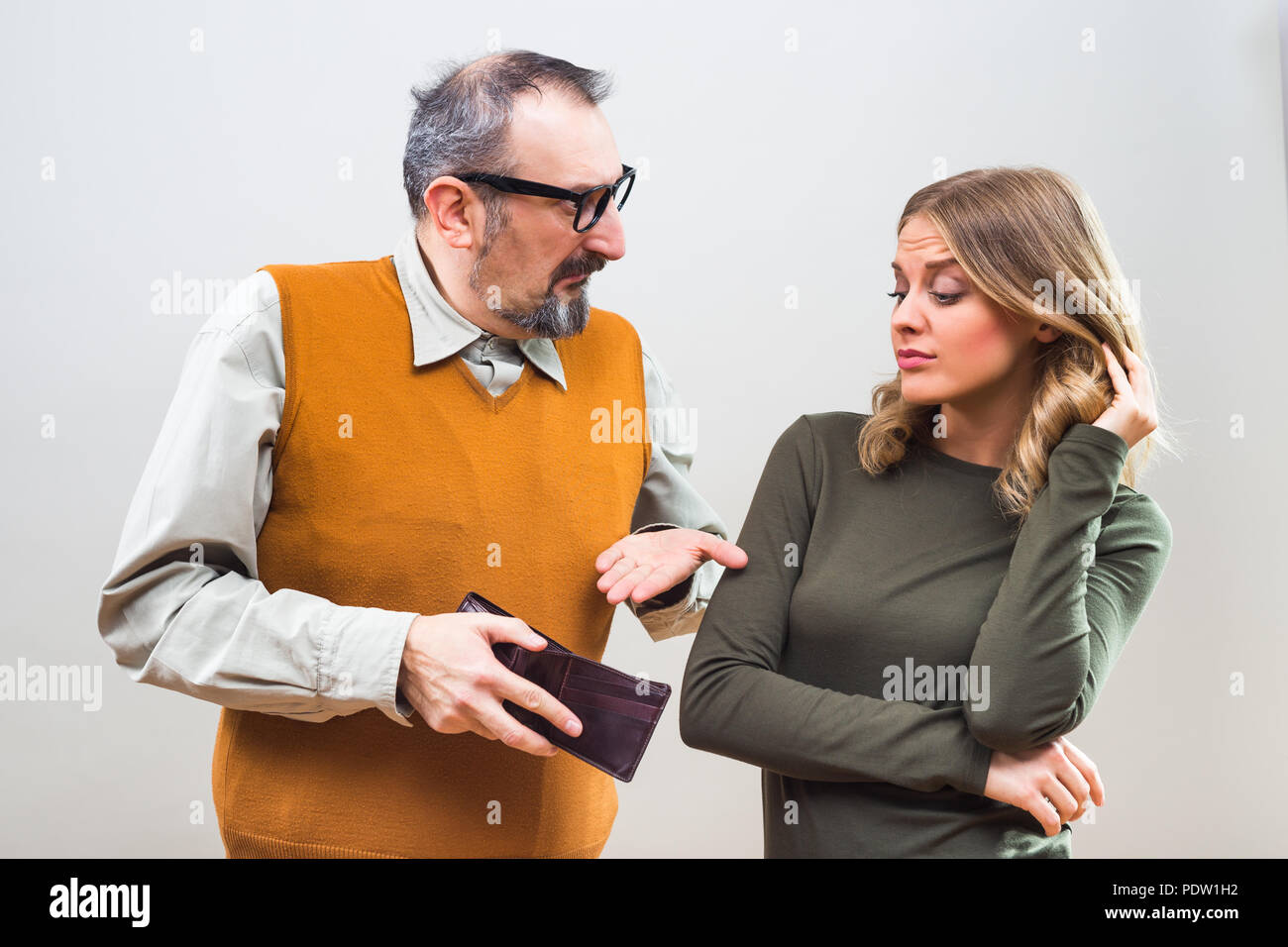 Nerdy man is showing to his beautiful wife that he doesn't have any more money and she is disappointed. - Stock Image