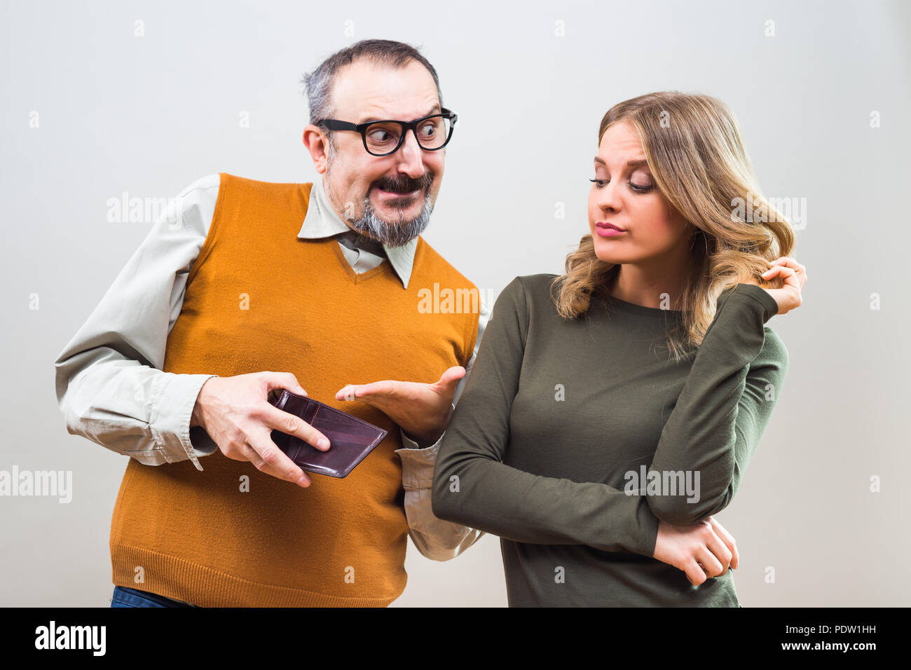 Nerdy man is trying to get attention from a beautiful woman by showing her his wallet full of money but she is still not interested. - Stock Image