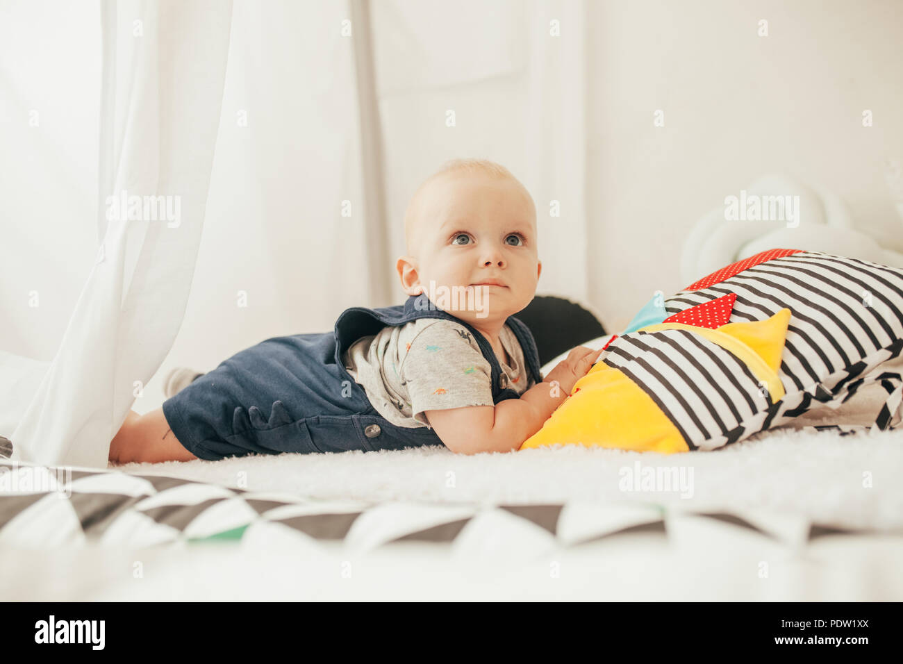 Toddler in rompers and t-shirt lies on bed next to colorful pillows. - Stock Image