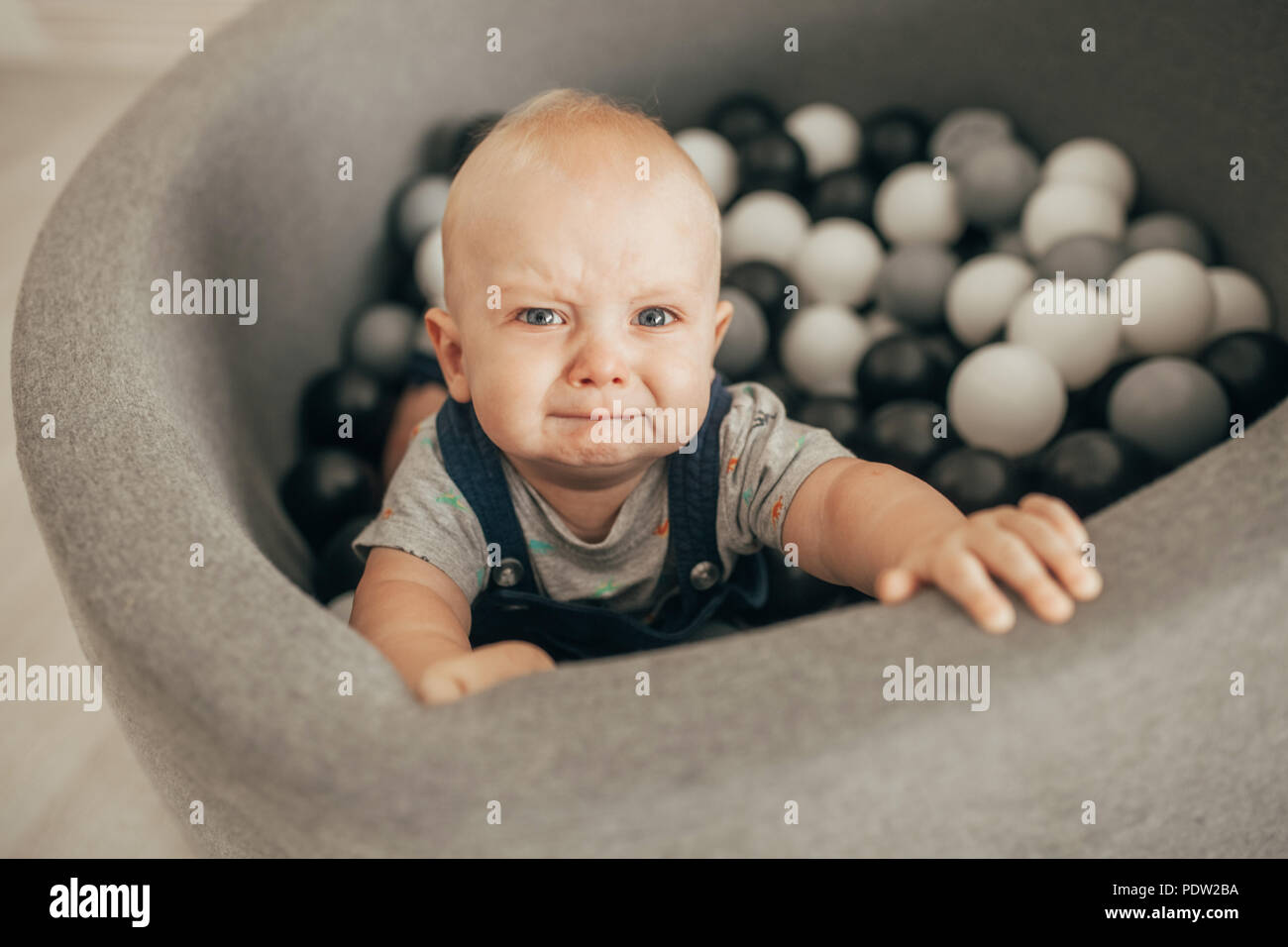 Tearful toddler stands in basket with small balls and cries. Top view. - Stock Image