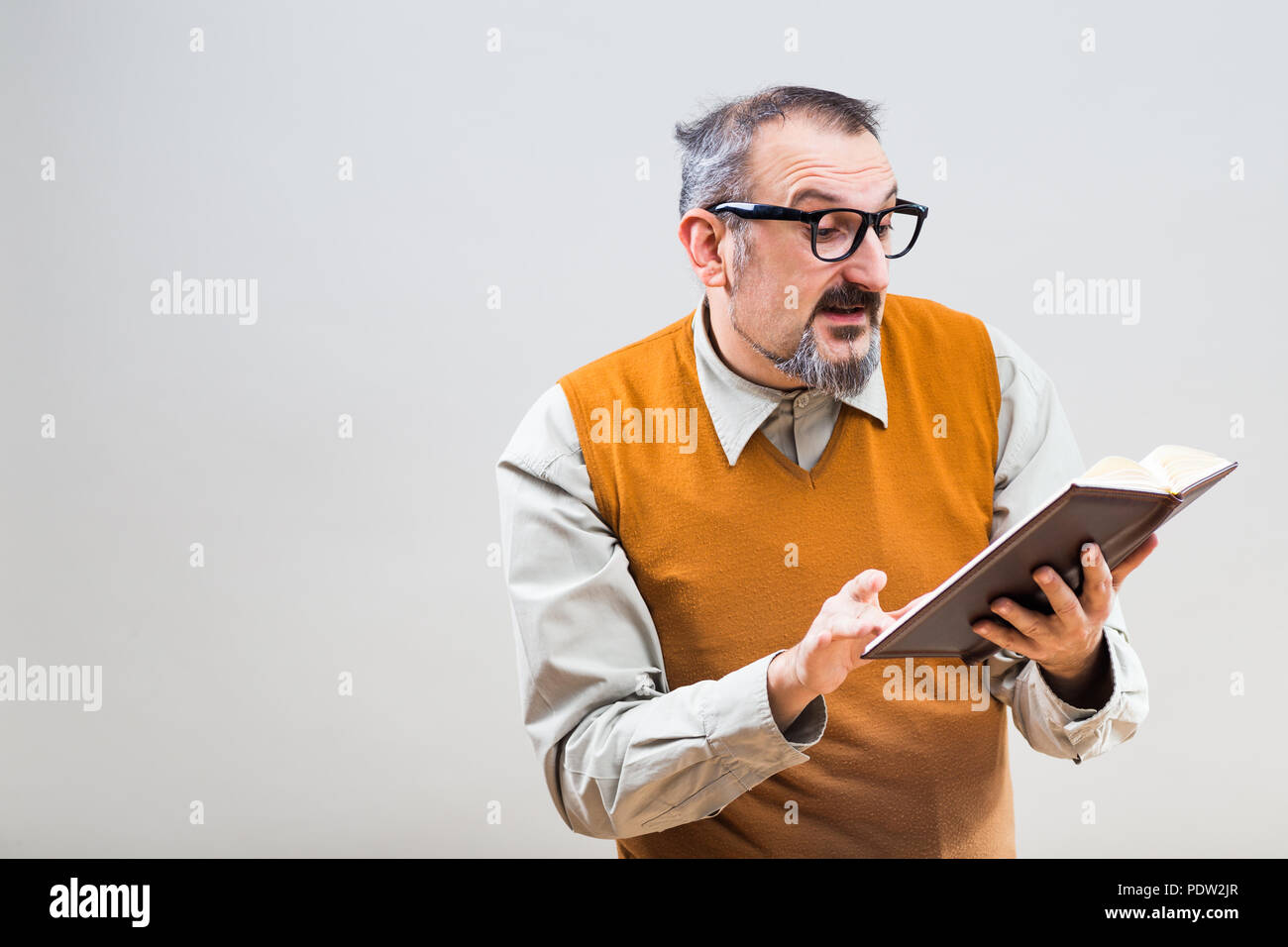 Nerdy businessman is holding his personal organizer and working. - Stock Image