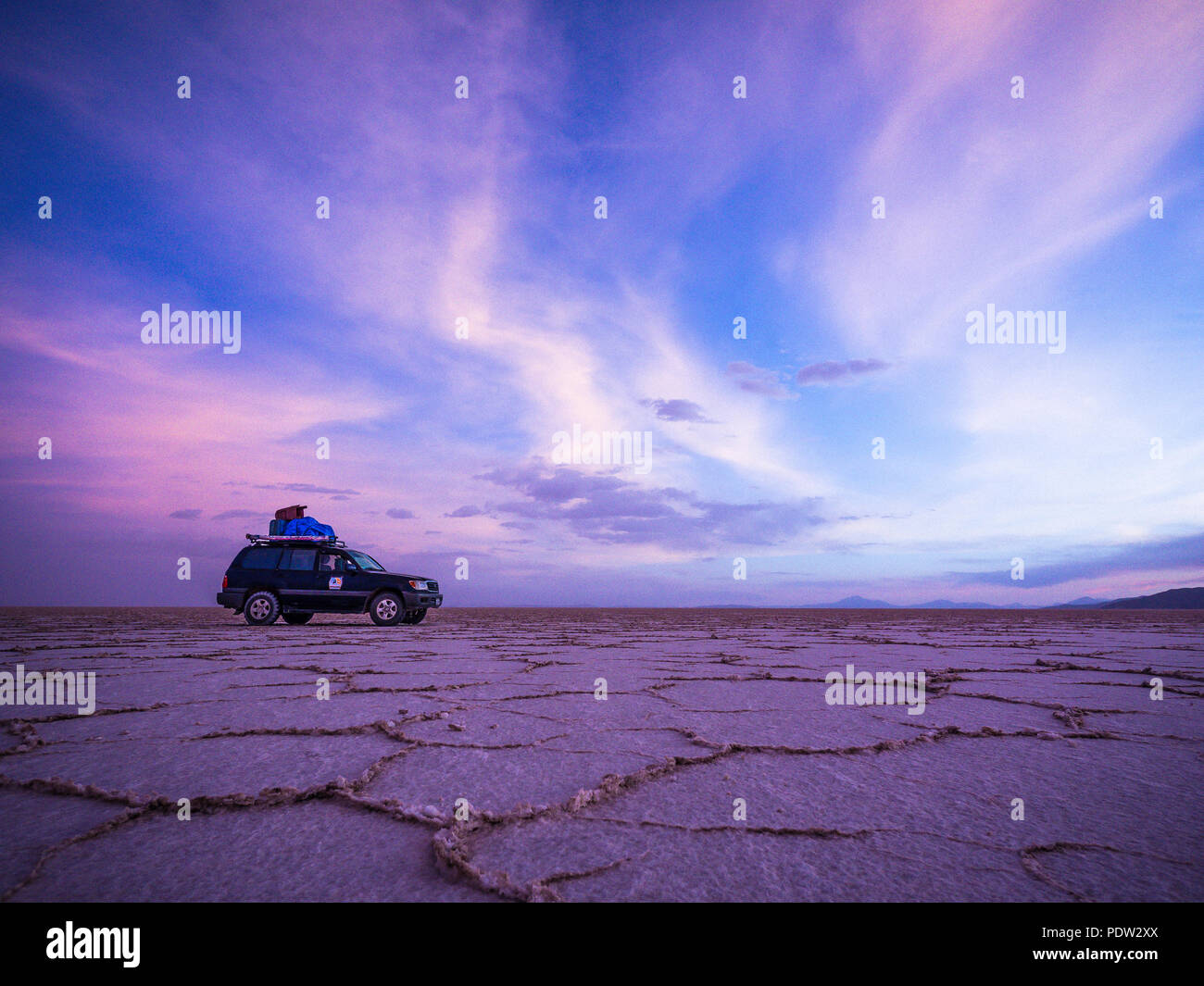 4WD jeep on the horizon of Salar de Uyuni Salt Flat in Bolivia - Stock Image