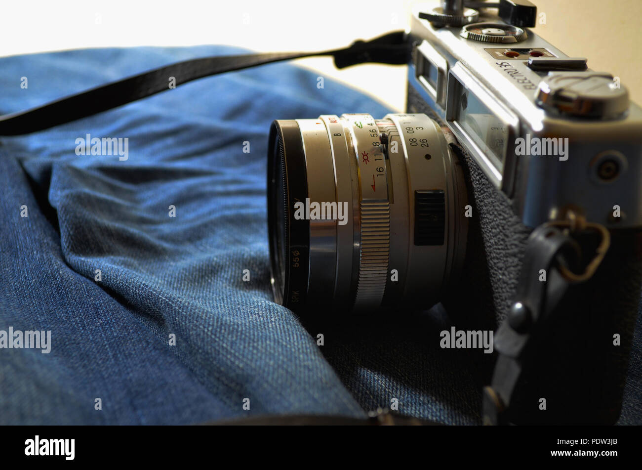 Traveller: Old SLR Camera and old jeans - Stock Image
