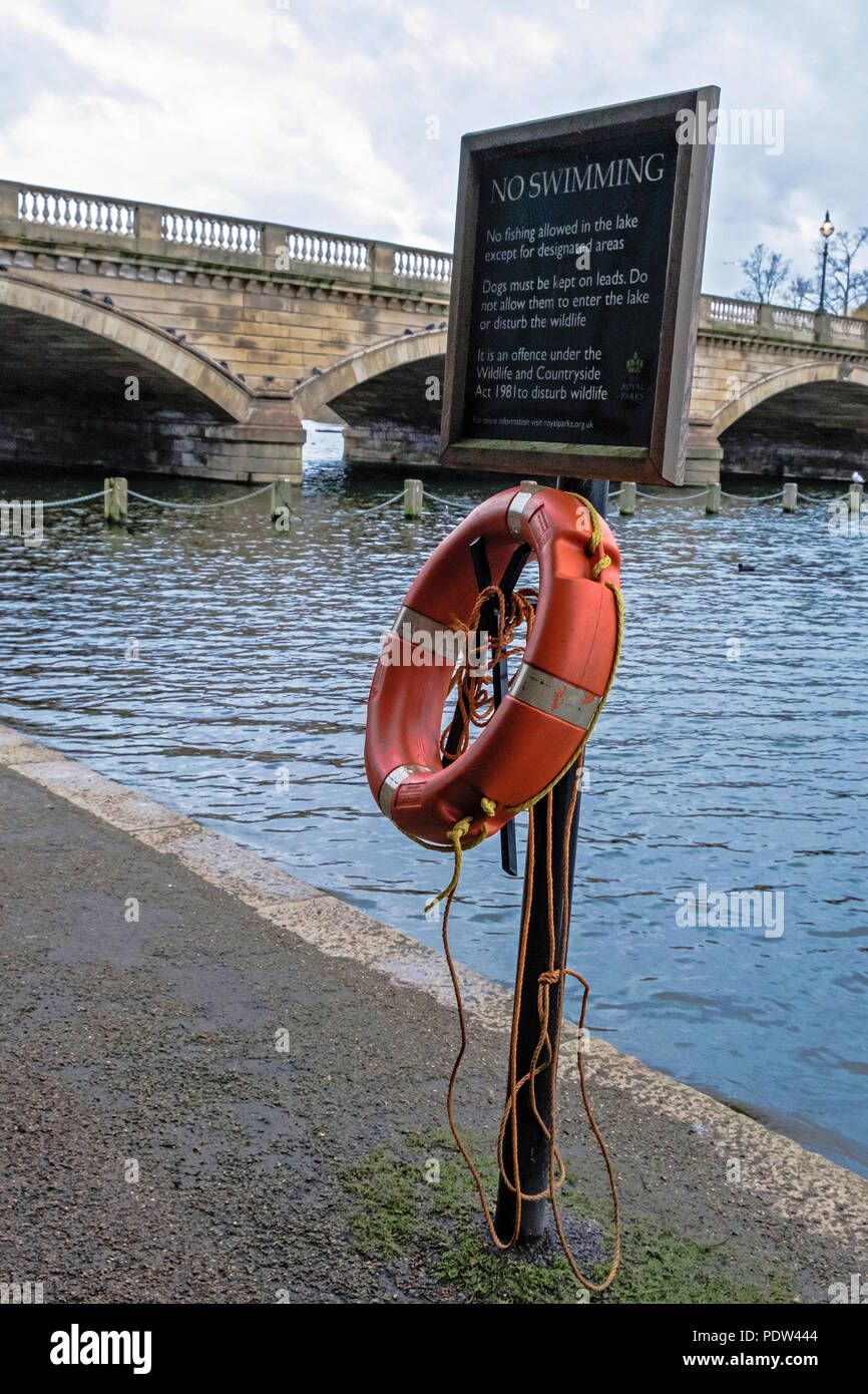 No swimming sign with Life Saver at Hyde Park next to Serpentine Lake. The Serpentine Bridge in background. Portrait. No People. - Stock Image