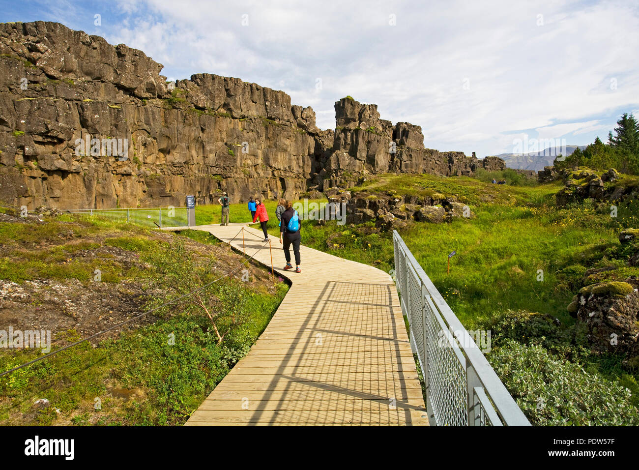 Hikers wander the wild land of Pingvellir (Thingvellir) National Park in South Iceland, the site of Iceland's first parliament, and home to the summer - Stock Image