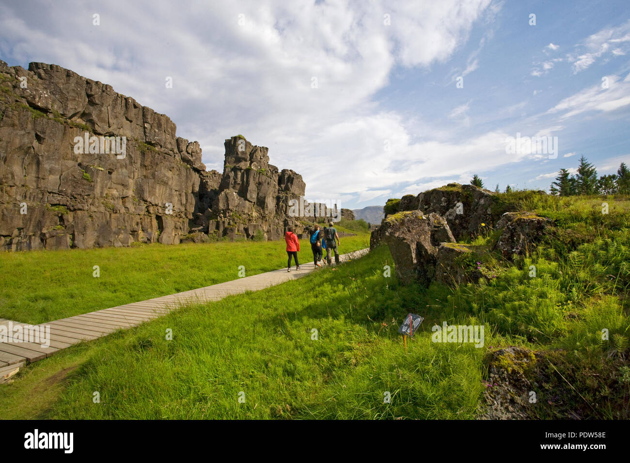 Hikers wander the famous Almannagja Gorge, in Thingvellir National Park, in south Iceland. - Stock Image