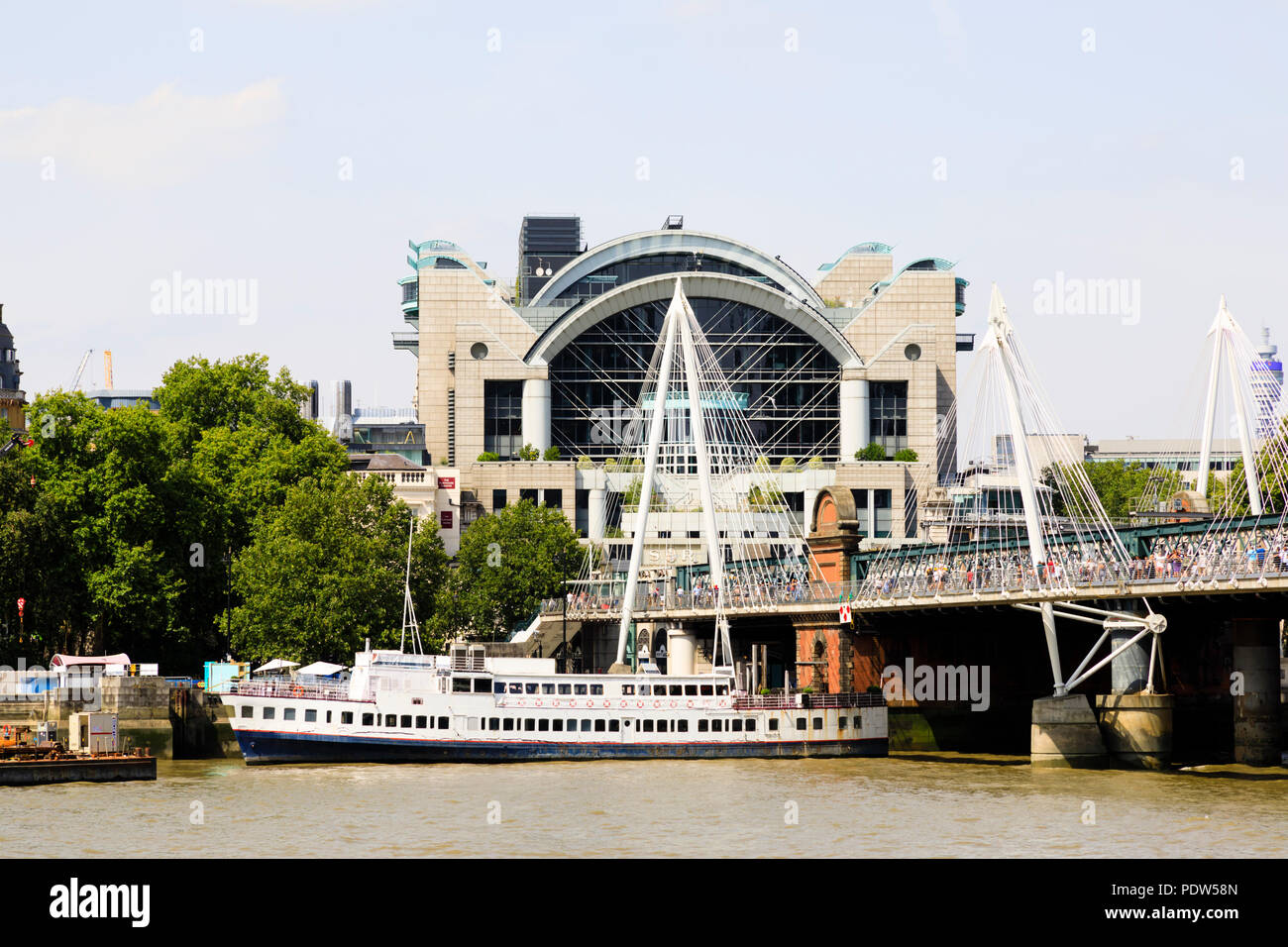 Charing Cross rail station on the North bank of the River Thames, London. The R.S. Hispaniola, floating restaurant is moored at Victoria Embankment. t - Stock Image