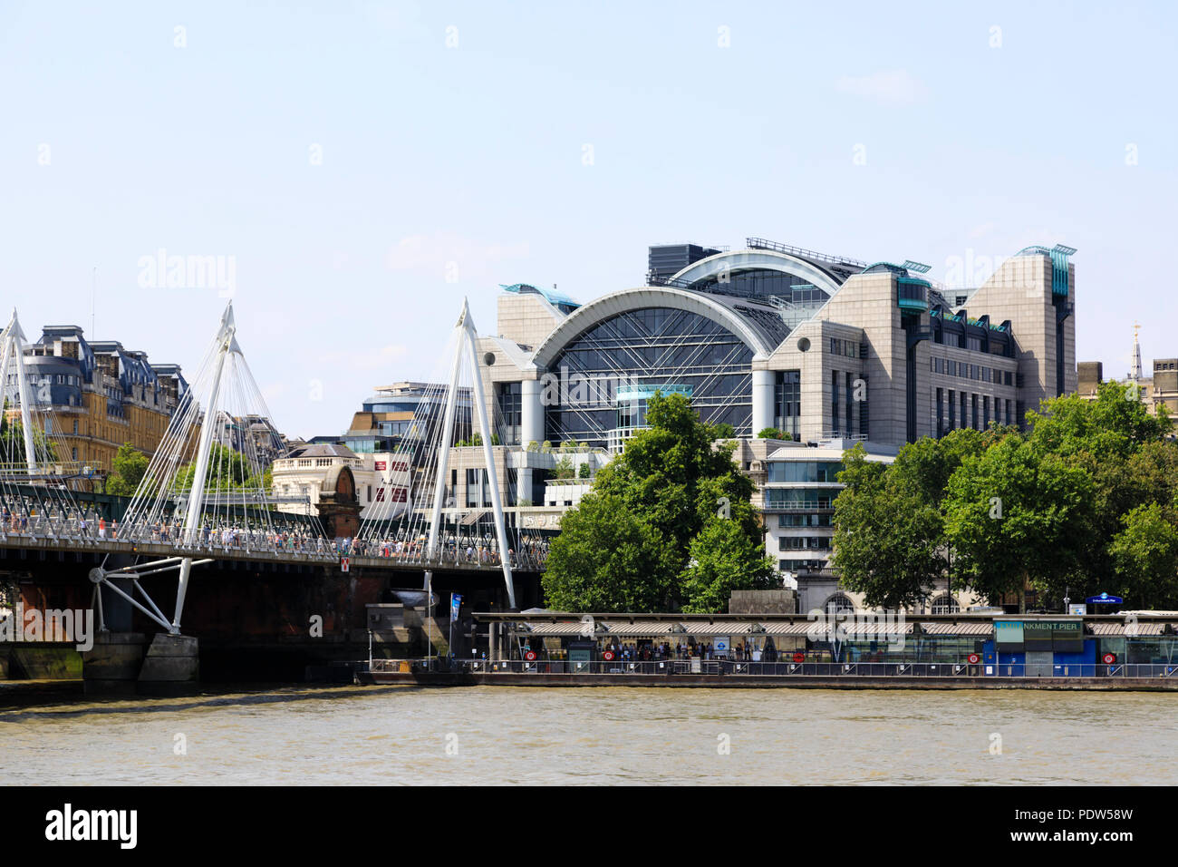 Charing Cross railway station on the north bank of the River Thames, London. Hungerford and Golden Jubilee bridge with crowds of tourists. - Stock Image