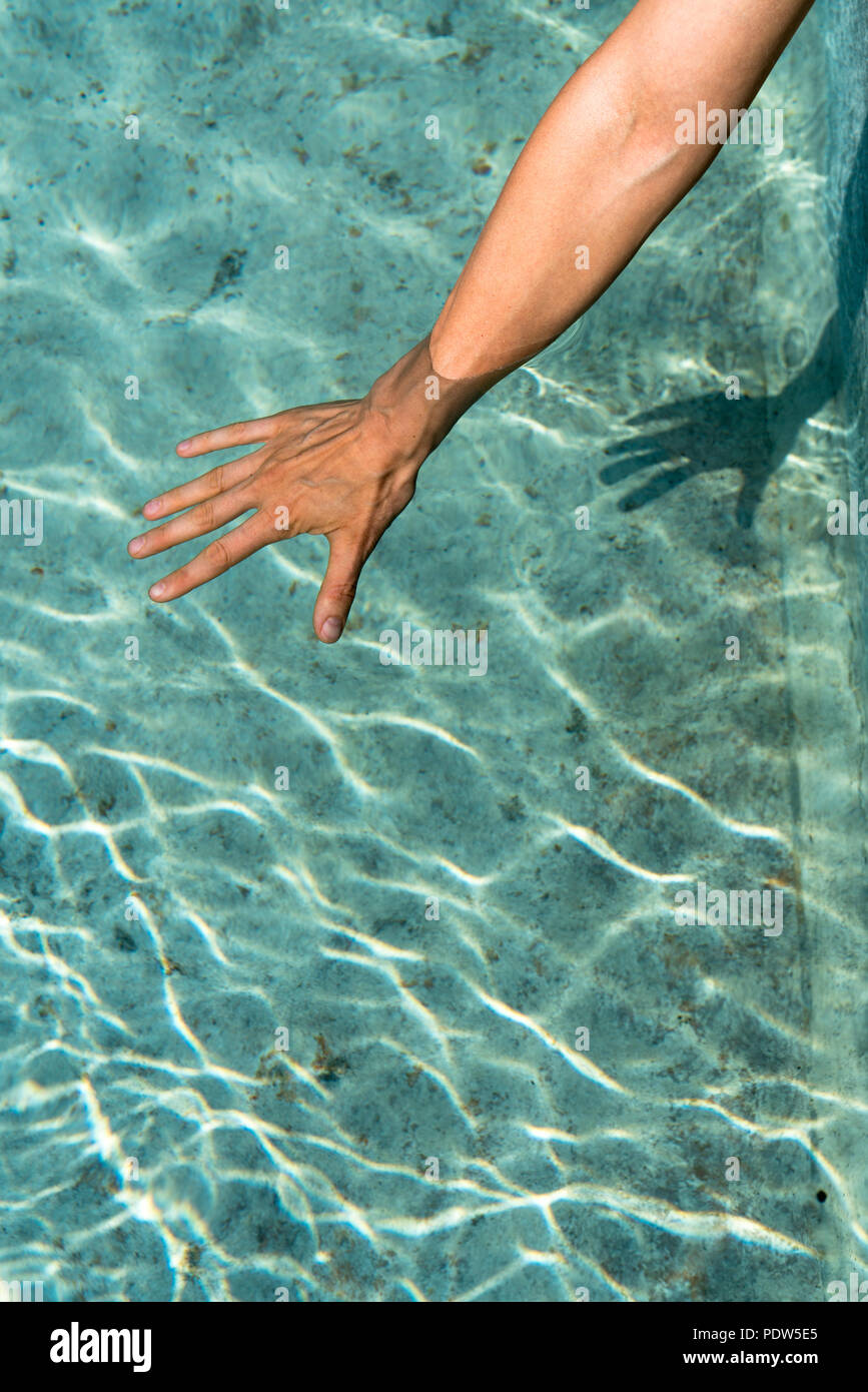 A female hand dipping into the cool turquoise water of an old traditional stone fountain basin - Stock Image