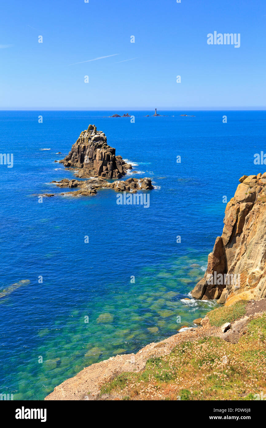 Armed Knight sea stack and distant Longships Lighthouse off Land's End from the South West Coast Path, Sennen, Cornwall, England, UK. - Stock Image