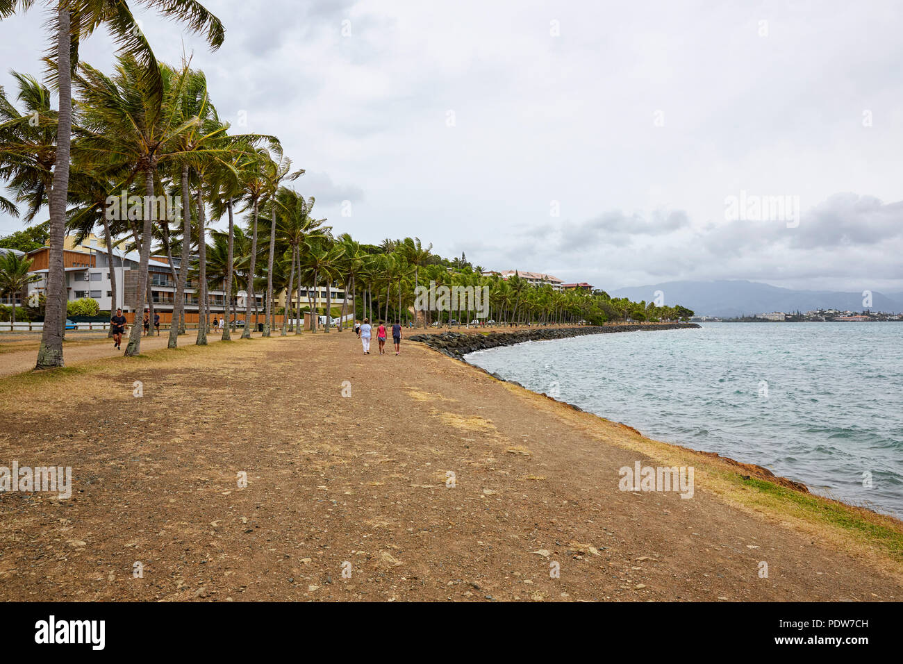 People walking stralling on the Pierre Vernier Promenade in Noumea New Caladonia (Nouvelle Caledonie) Baie des Petroles - Stock Image