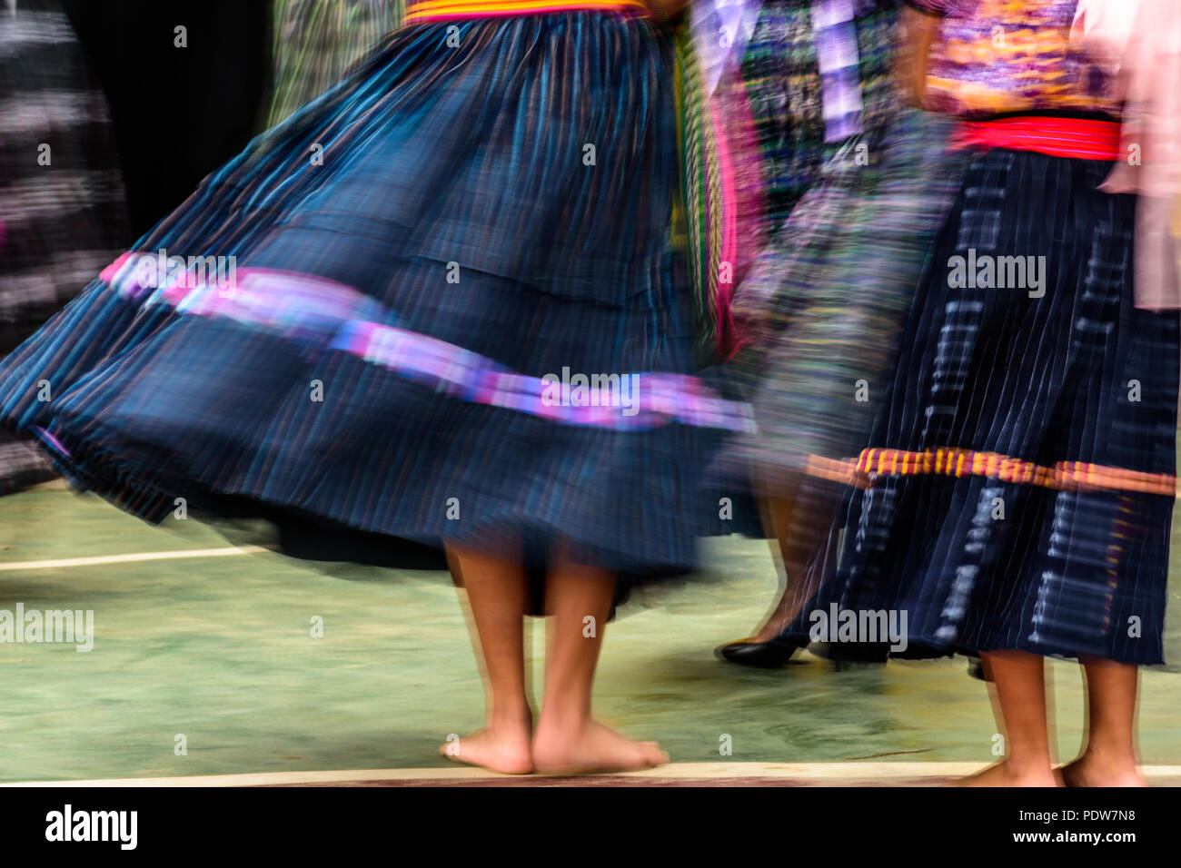 Swirling skirts of traditional Guatemalan folk dancers caught in blur of color and movement. - Stock Image