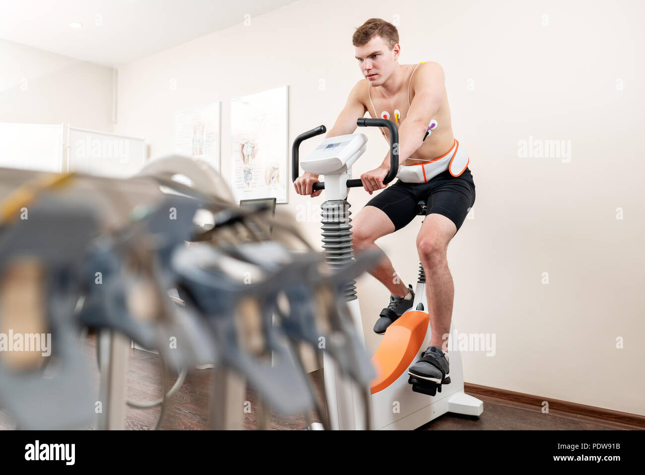 A male patient, pedaling on a bicycle ergometer stress test system for the function of his heart checked. Athlete does a cardiac stress test in a medical study, monitored by the doctor. - Stock Image