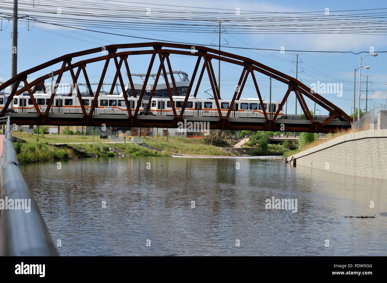 A light rail train crossing the river with Invesco Field in the background. Exclusive Denver stock photos - Stock Image