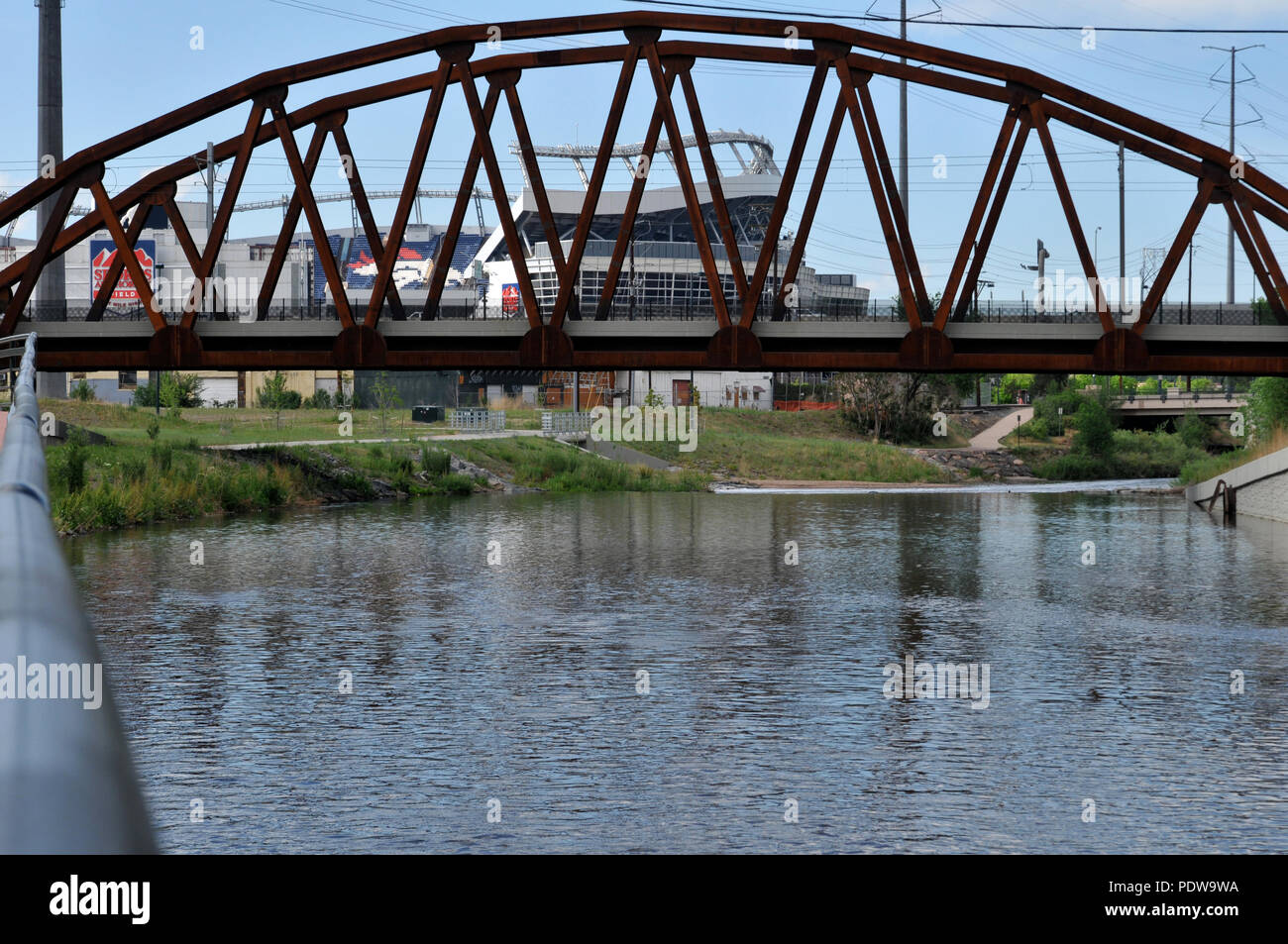 Invesco Field seen through a bridge crossing the South Platte River.  Exclusive Denver stock photos. - Stock Image