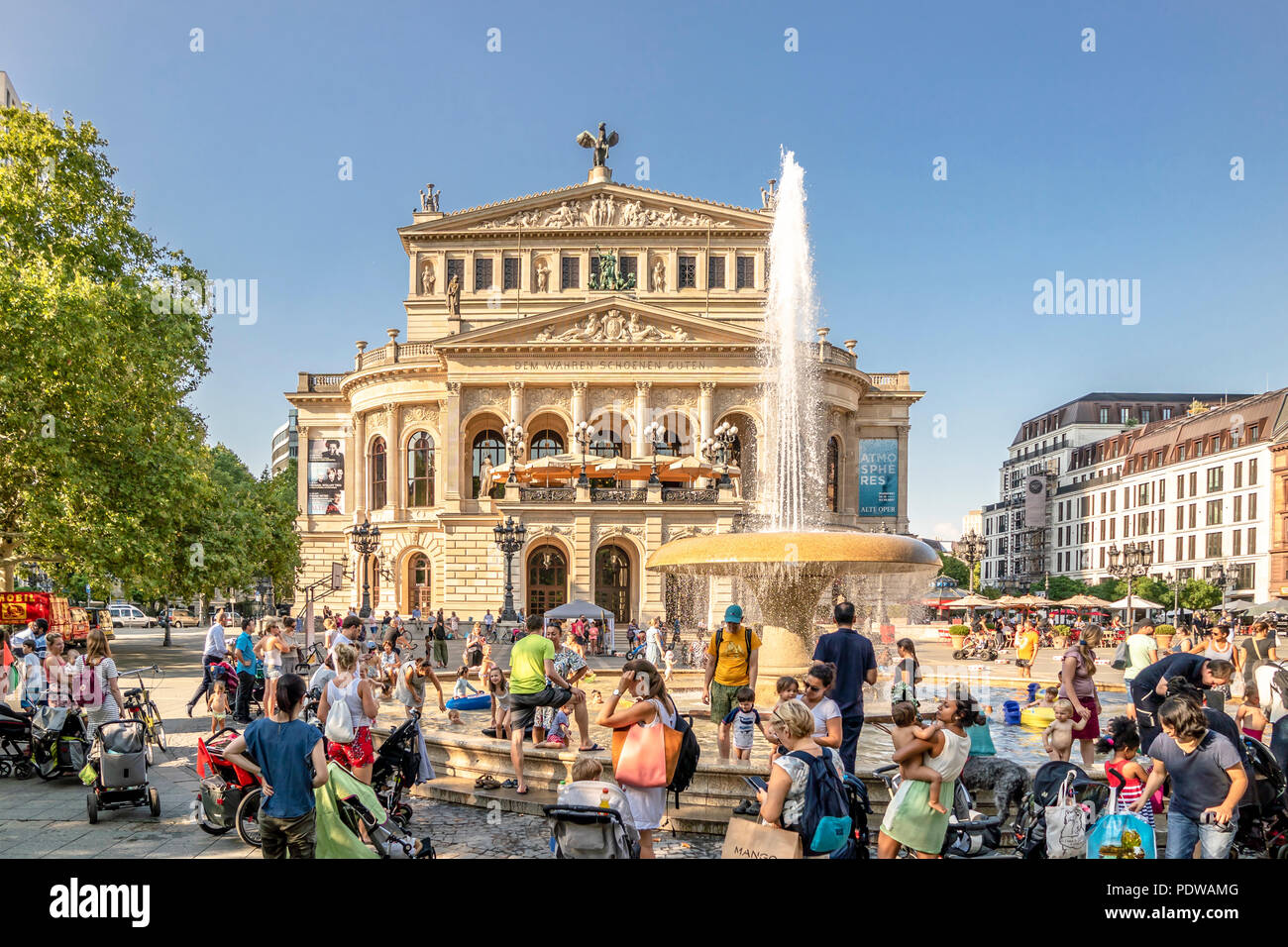 FRANKFURT / GERMANY - AUGUST 02 2018: People searching for refreshment in the water of the fountain at Opernplatz during one of the warmest summer day - Stock Image
