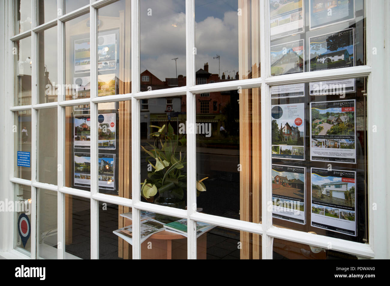 properties in the window of an upmarket estate agency window chester cheshire england uk - Stock Image